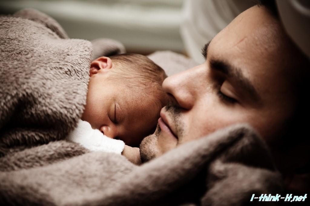 父親の横でスヤスヤと眠る赤ちゃん