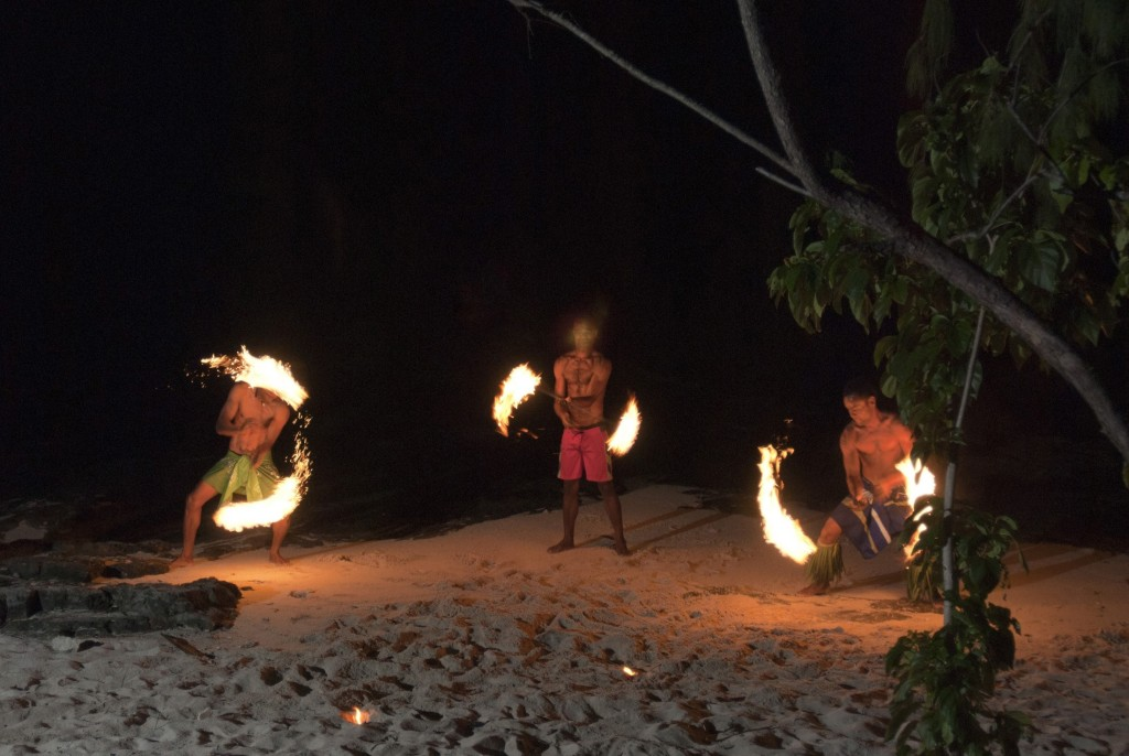 Three Fijian men performing a fire dance on the beach twirling flaming branches in the night sky