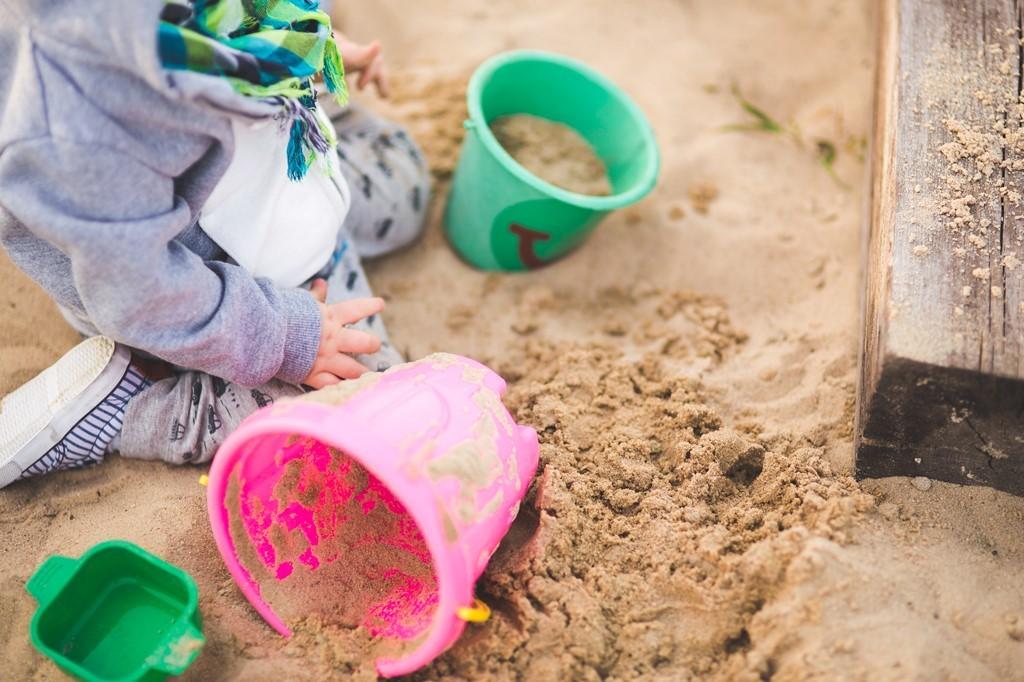 砂場で服を汚して遊ぶ子供