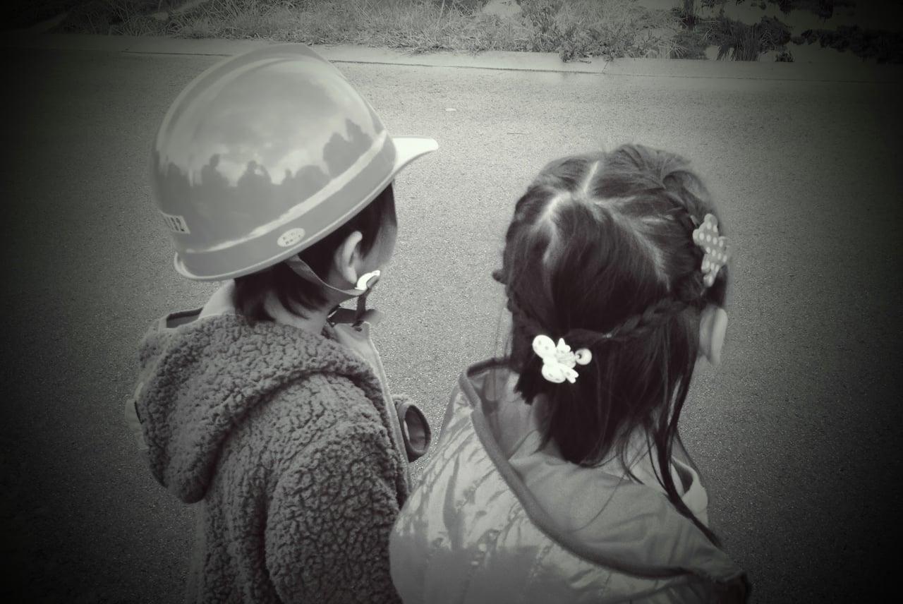ヘルメットを被った男の子と横に並ぶ女の子