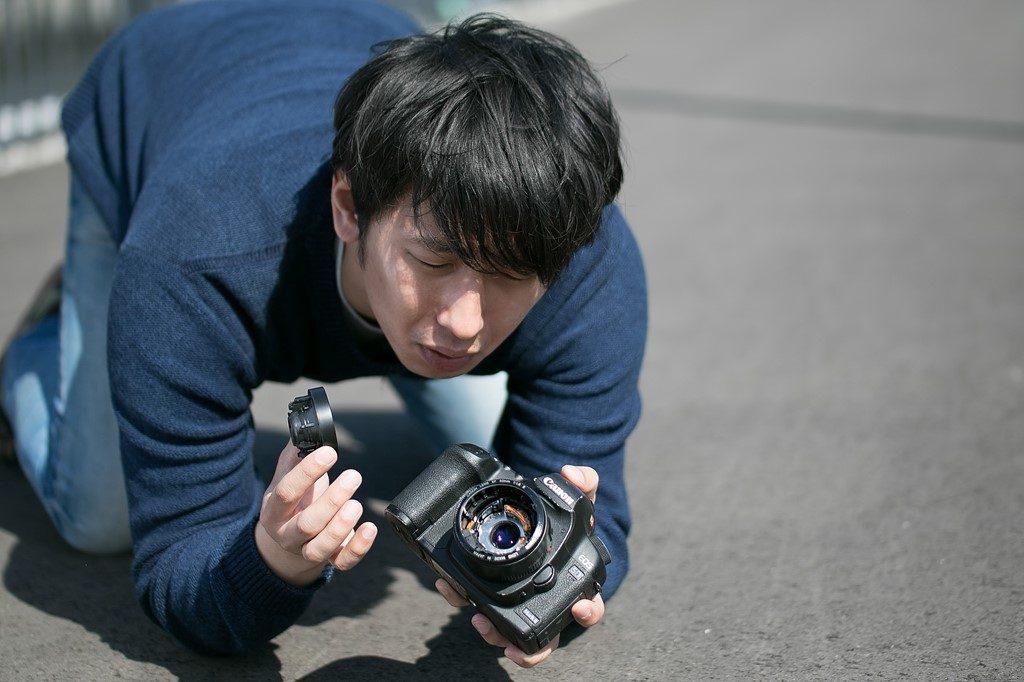 カメラを落として壊れたのを見て悲しむ男性