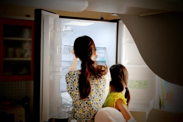 冷蔵庫の前に立つ妻と子供