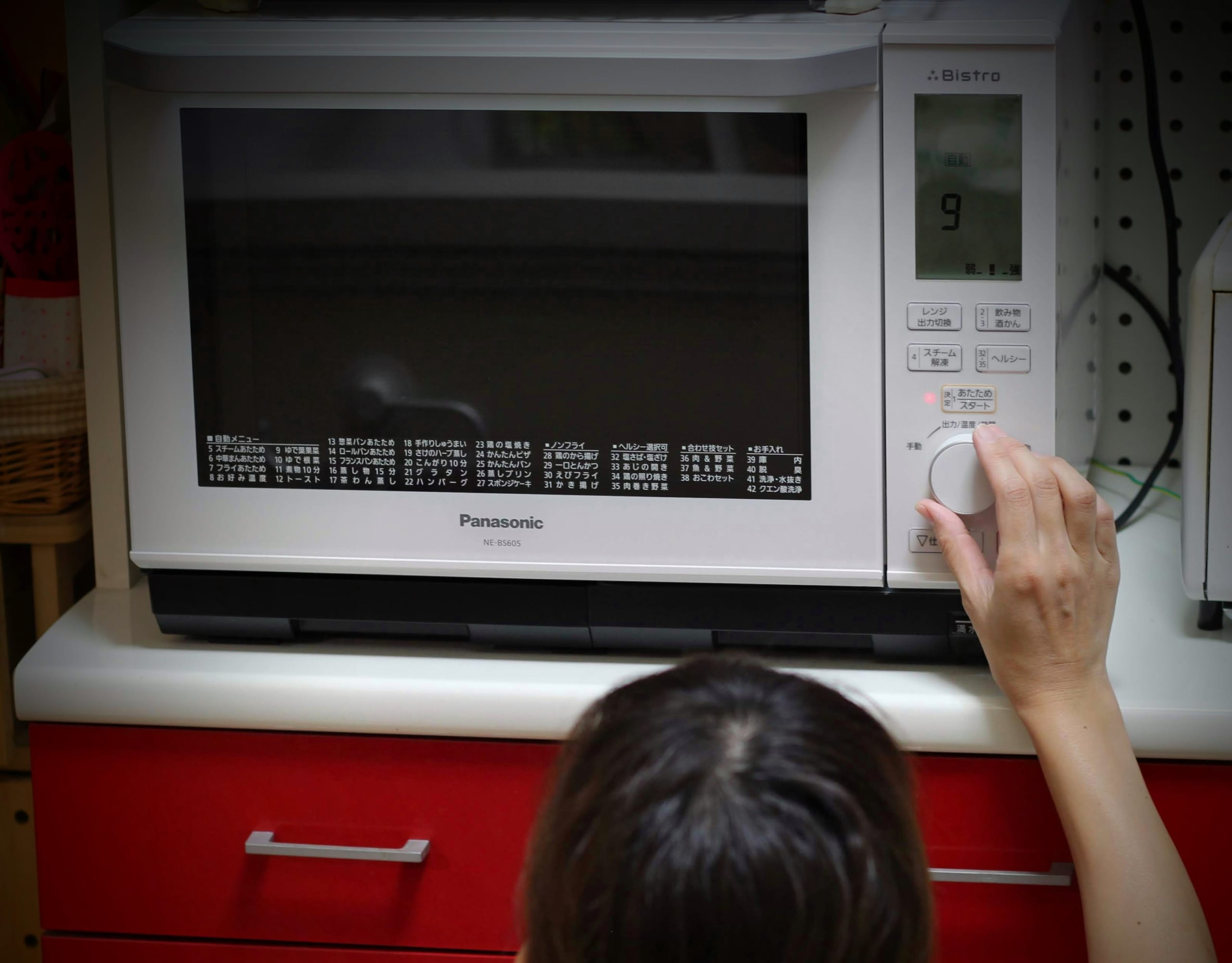 購入したオーブンレンジを操作する女性